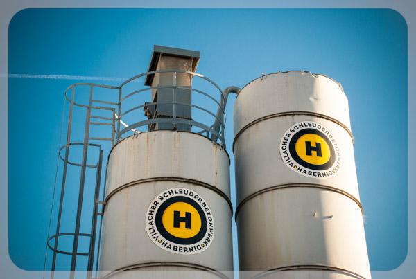 Foto Silos mit dem gelb-schwarzen Logo der Firma Villacher Schleuderbetonwerk Habernig GmbH